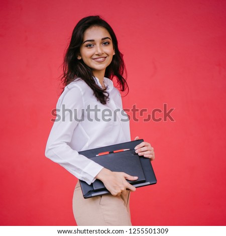 Portrait of a young Indian Asian student girl wearing a white shirt and khakis as she holds her laptop and notebook. She is smiling confidently and is tall, elegant and attractive.