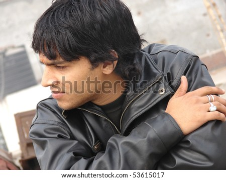 portrait of a young indian man wearing leather jacket - stock photo