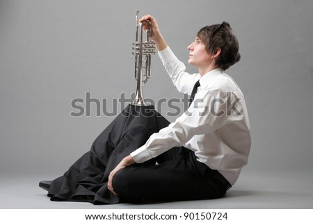 Portrait of a young jazz man and his Trumpet grey background