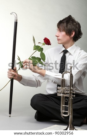 Portrait of a young jazz man andTrumpet grey background. Love melody