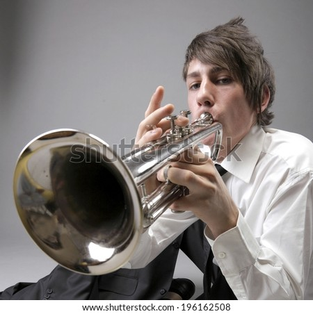 Portrait of a young jazz man playing his Trumpet grey background. Love melody