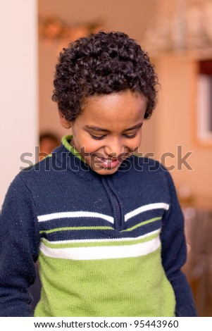 Portrait of a young kid looking down with with a smirk and bit of shyness