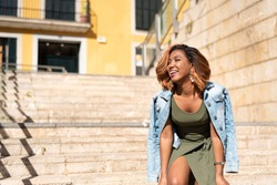 Portrait of a young latin black woman smiling, laughing, posing in front of a camera with a green dress and jean jacket on a hot summer day. Stylish hair. Lifestyle happy, urban photos