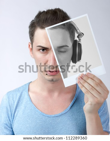 Portrait of a young male dressed in blue shirt, holding a vintage photo of himself with an eye closed and headphones on his head,remembering the time when he was a deejay - conceptual