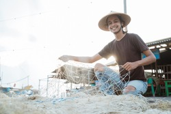 Portrait of a young male fisherman preparing a fishing net