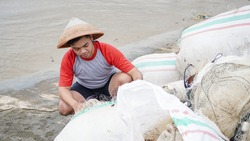 Portrait of a young male fisherman preparing a fishing net in beach