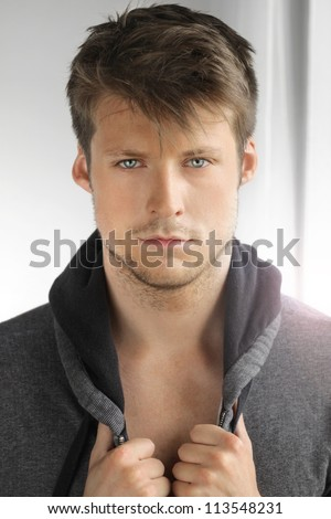 Portrait of a young male model with great face and hands on his jacket