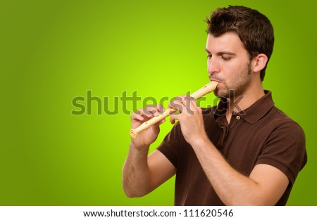 Portrait Of A Young Male Playing Flute On Green Background
