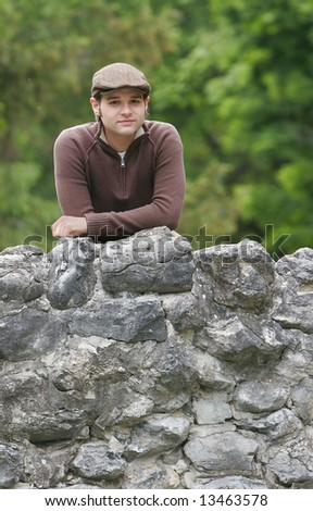 portrait of a young male with brown hair in the park on a stone bridge