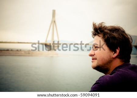 Portrait of a young man admiring the Rio Bridge in Greece. - stock photo