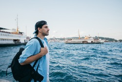 Portrait of a young man against the background of the sea, city, pier and ships. Tourist guy with a backpack on the background of the water and the panorama of the city near the marine station