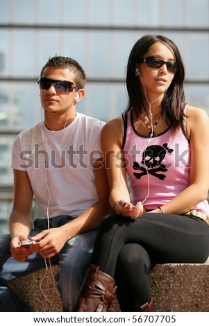 Portrait of a young man and a young woman listening to music with a mp3 walkman