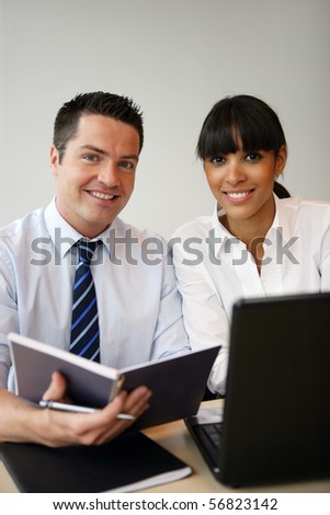 Portrait of a young man and a young woman smiling in front of a laptop computer - stock photo
