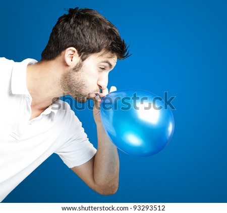portrait of a young man blowing a balloon over a blue background