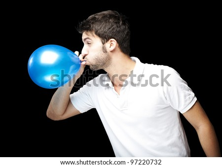 portrait of a young man blowing up a blue balloon against a black background