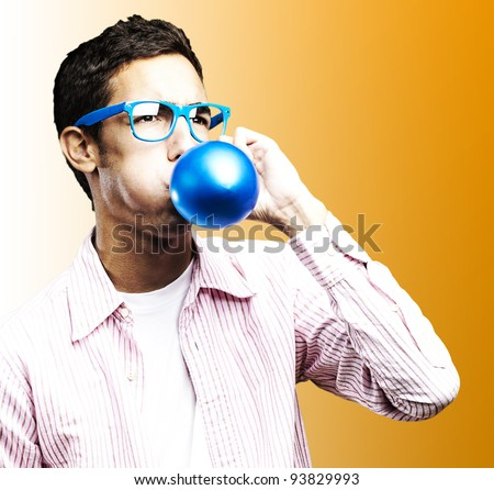 portrait of a young man blowing up a blue balloon against an orange background
