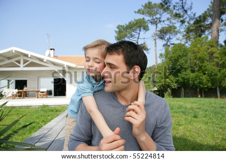 Portrait of a young man carrying a little boy on his back in front of a house