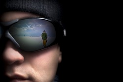 Portrait of a young man close up. In the glasses reflection the mountains and snowboarders