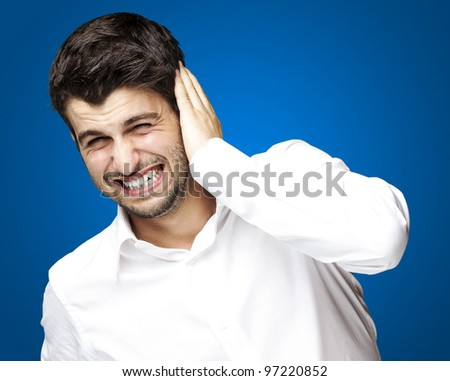 portrait of a young man covering his ear against a blue background