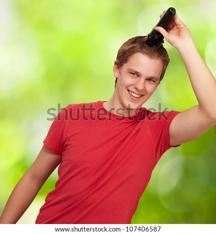 portrait of a young man cutting his hair against a nature background
