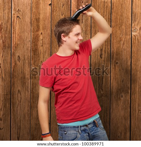 portrait of a young man cutting his hair against a wooden wall