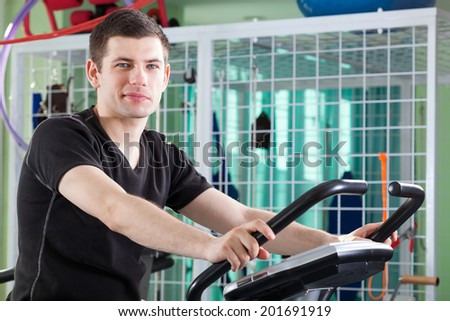 Portrait of a young man cycling on stationary bike
