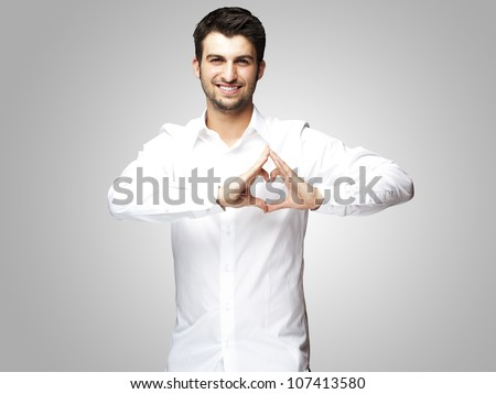 portrait of a young man doing a heart gesture against a grey background