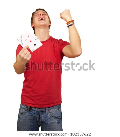 portrait of a young man doing a winner gesture playing poker over a white background