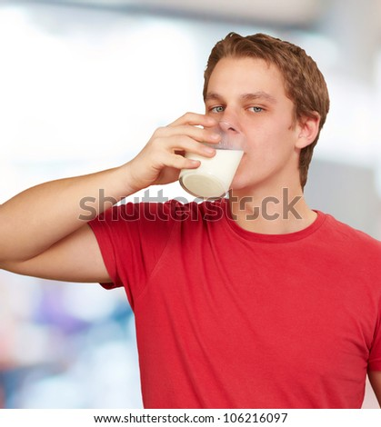 portrait of a young man drinking milk indoor