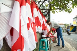 portrait of a young man folding the Indonesian national flag