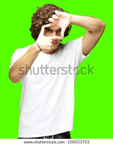 portrait of a young man gesturing a frame against a removable chroma key background