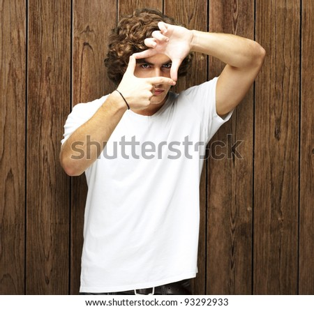 portrait of a young man gesturing a frame against a wooden wall