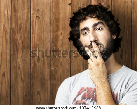 portrait of a young man having an idea against a wooden wall