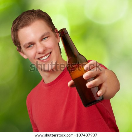portrait of a young man holding a beer against a nature background