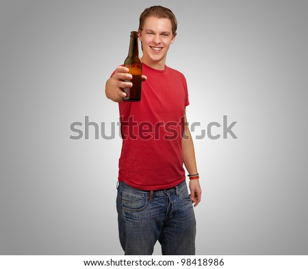 portrait of a young man holding a beer bottle against a grey background