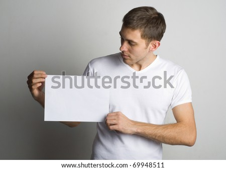 Portrait of a young man holding a blank board for text near the wall
