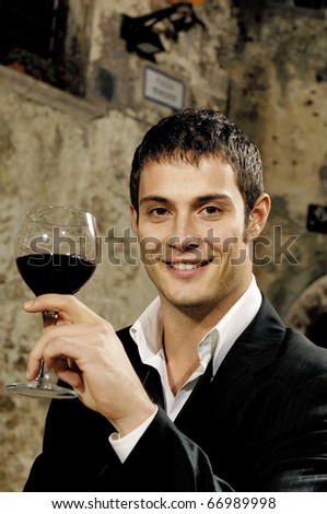 Portrait of a young man holding a glass of red wine