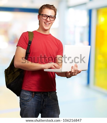 portrait of a young man holding a laptop and wearing a backpack indoor