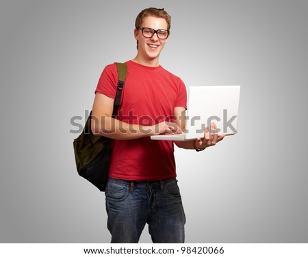 portrait of a young man holding a laptop and wearing a backpack over a grey background