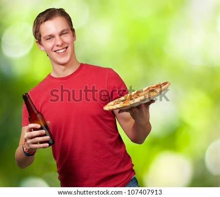 portrait of a young man holding a pizza and a beer against a nature background