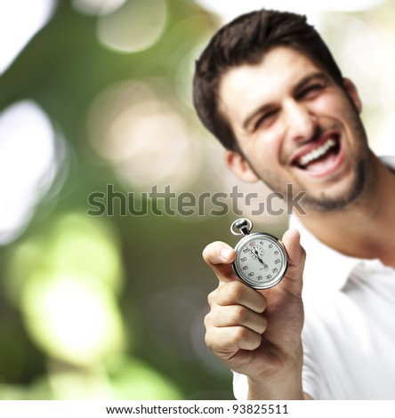 portrait of a young man holding a stopwatch against an abstract background