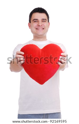 Portrait of a young man holding heart shape pillow over white background