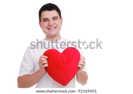Portrait of a young man holding heart shape pillow over white background - stock photo