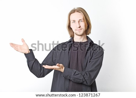 Portrait of a young man in a black shirt with long blond hair, showing something. on a white background - stock photo