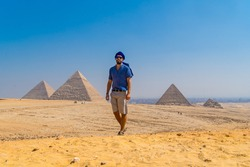 Portrait of a young man in a blue turban walking next to the Pyramids of Giza, the oldest Funerary monument in the world. In the city of Cairo, Egypt