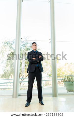 Portrait of a young man in a suit standing inside a large office