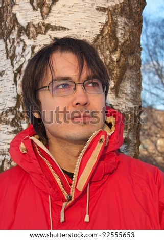 Portrait of a young man in winter forest on the birch background