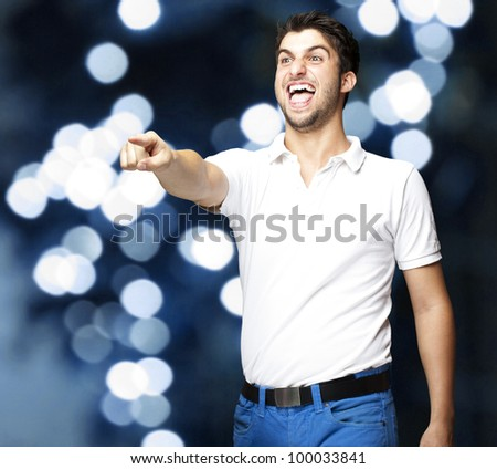portrait of a young man joking against a blue light background