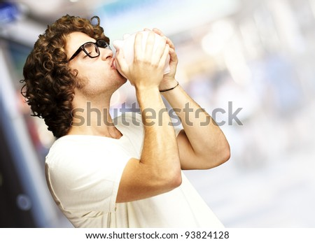portrait of a young man kissing a piggy bank at a crowded place