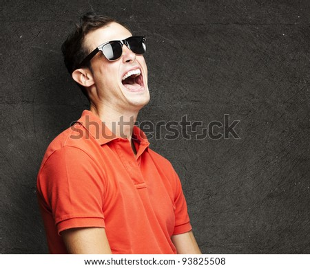 portrait of a young man laughing against a grunge wall